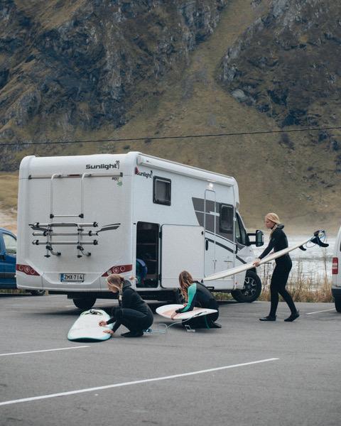 Naiset ottamassa surffilautoja ulos matkailuauton takatallista.