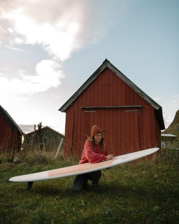 Laura Saarinen huoltaa surffilautaa Hoddevikin rannalla.