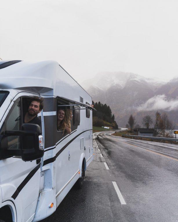 Kuskin vuorossa oleva Joonas ja matkustajana oleva Laura kurkistavat matkailuauton ikkunoista ulos.