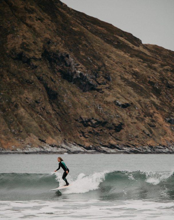 Laura surffaa Hoddevikin rannan aalloissa.