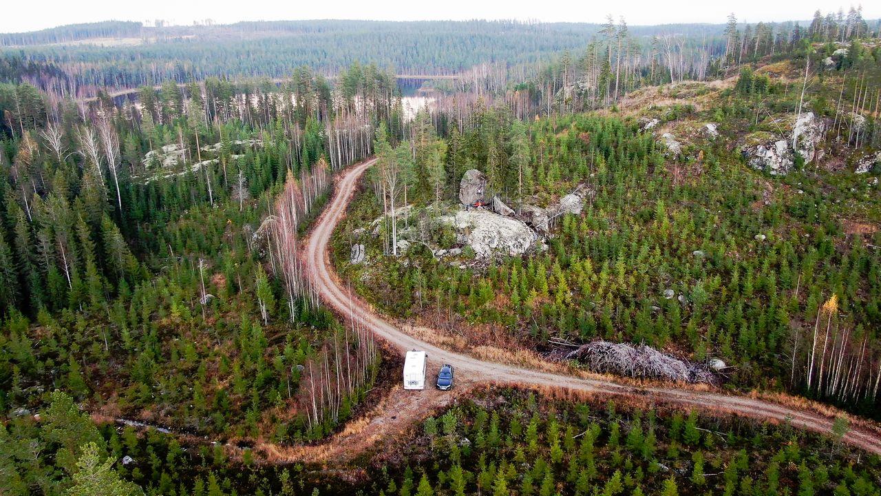 Matkailuauto pysäköitynä metsätien varrelle Itä-Suomessa.