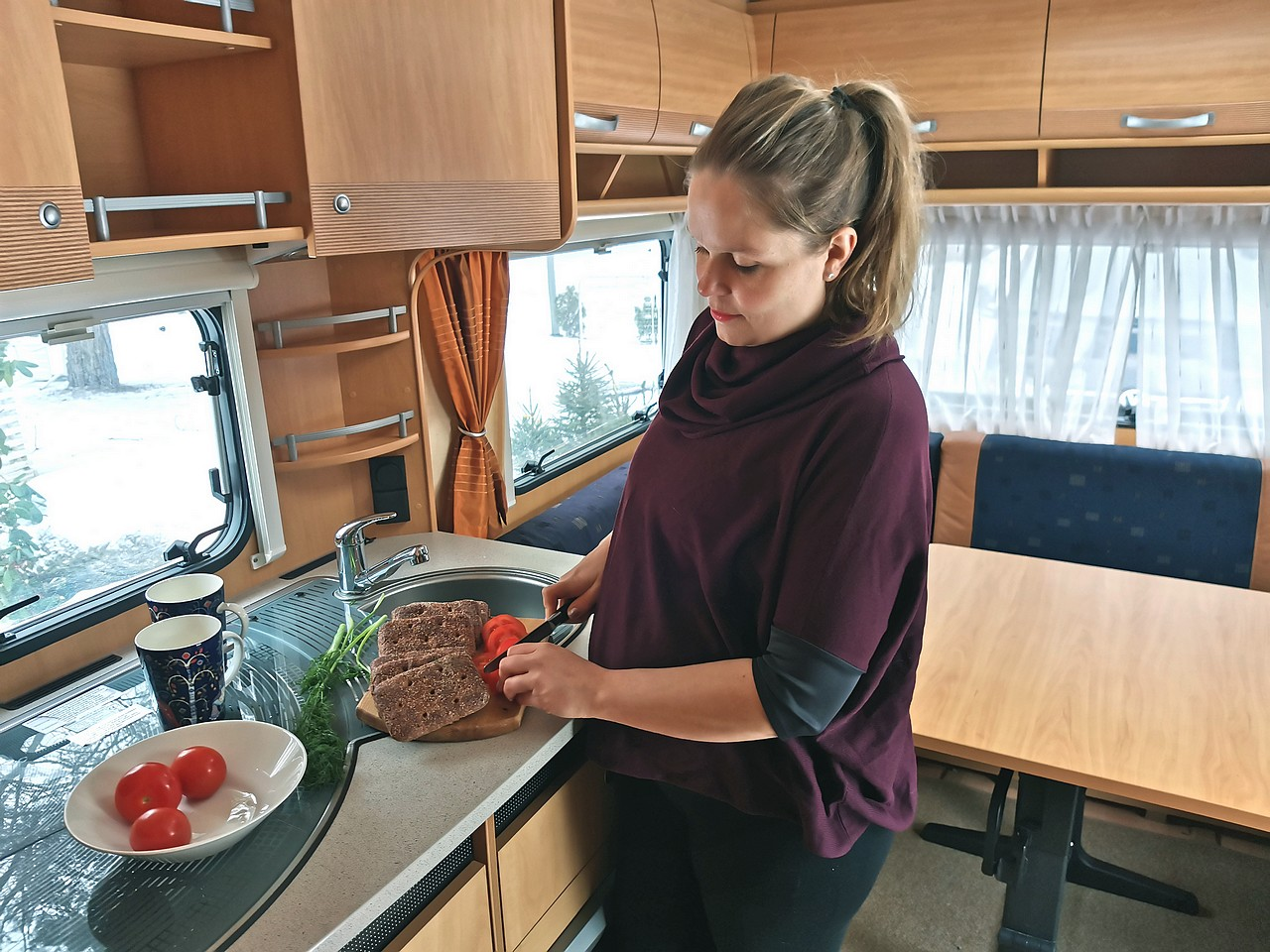Äiti laittaa leipiä asuntovaunun keittiössä.