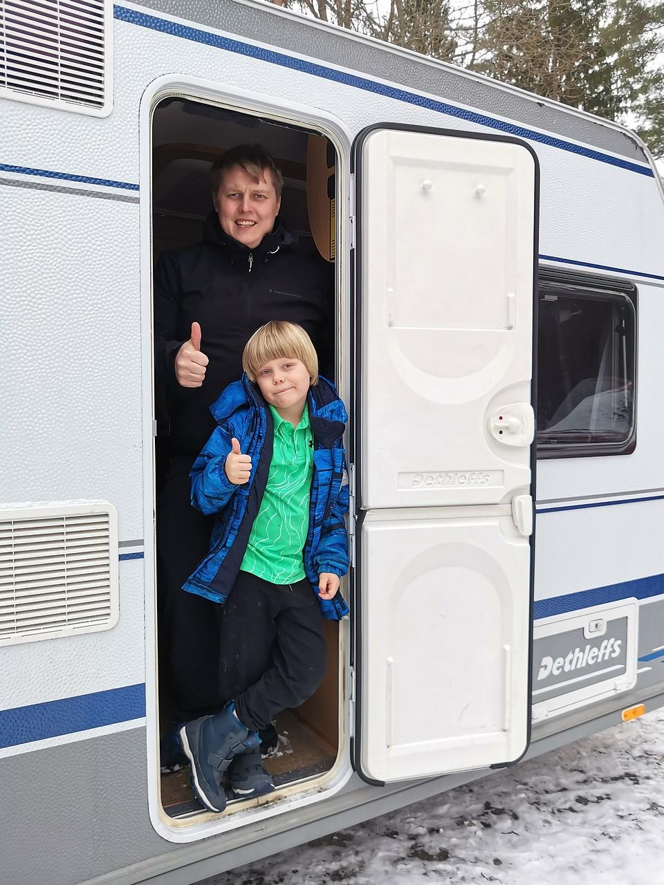 Isä ja poika asuntovaunun ovella peukut pystyssä.
