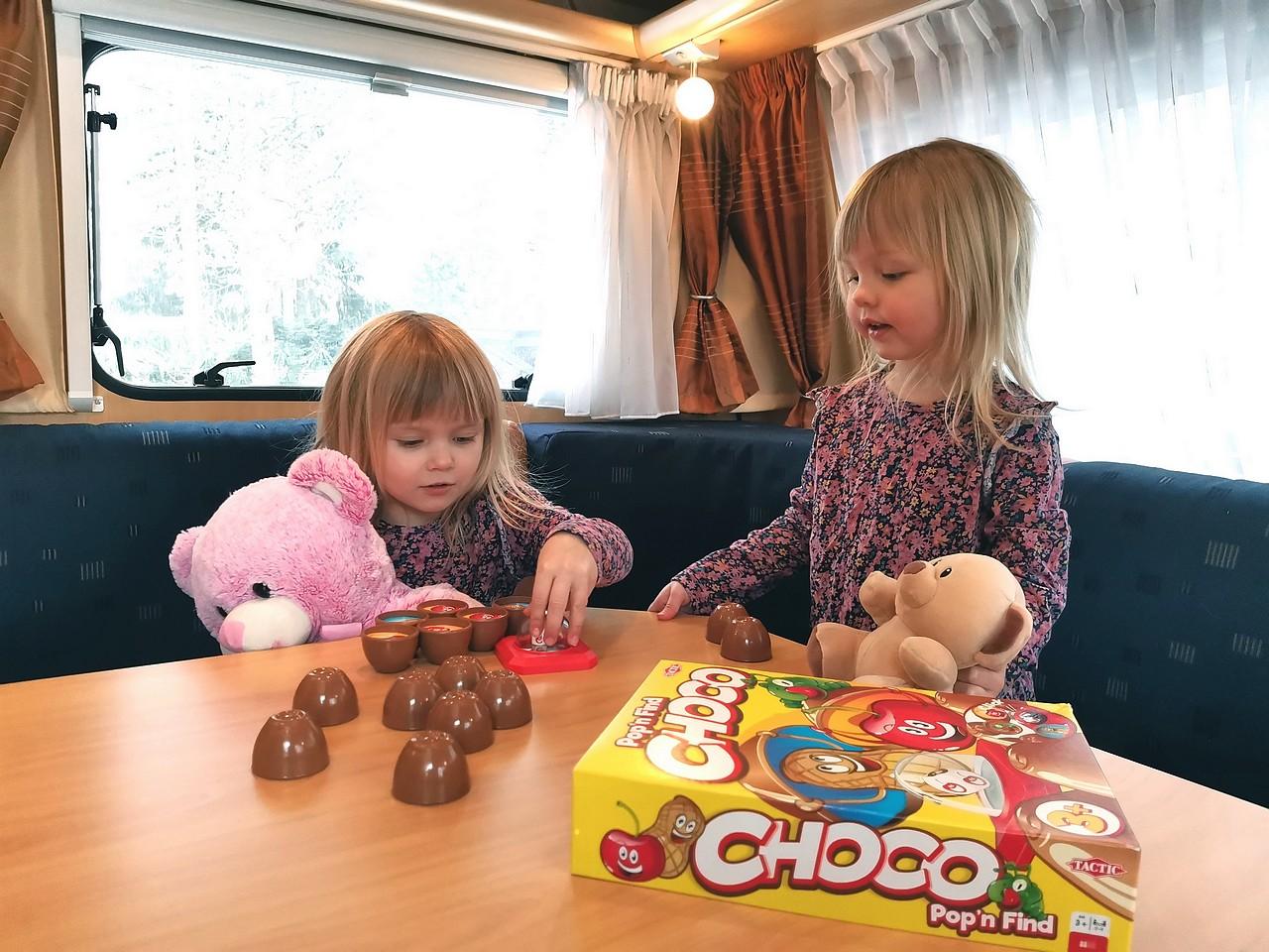 Perheen tytöt leikkivät asuntovaunun ruokapöydän ääressä.