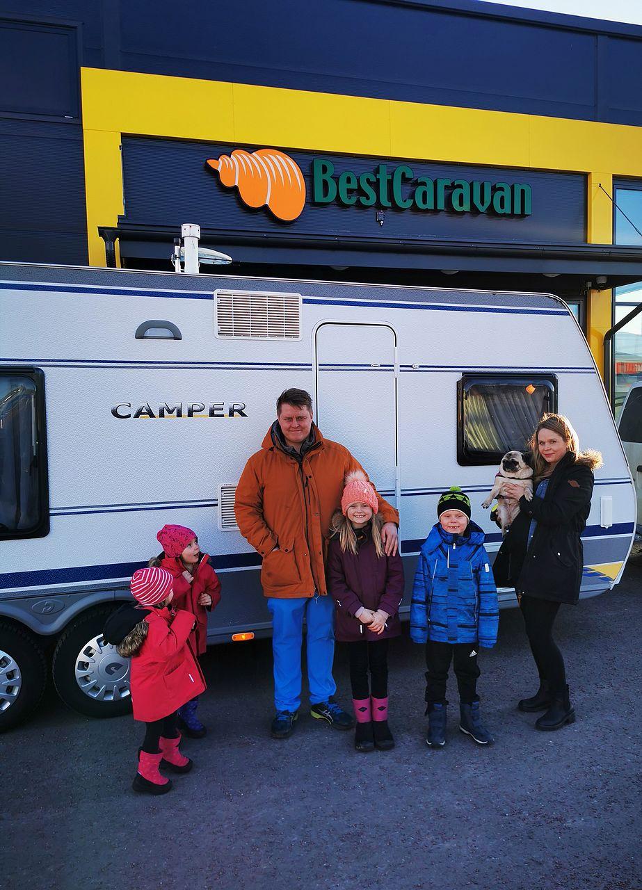 Asuntovaunu suurperheelle löytyi Best-Caravanilta - tyytyväiset omistajat vaunun edessä.