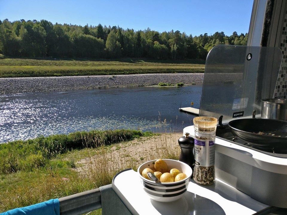 Perunat matkailuauton keittiötasolla taustalla jokimaisema