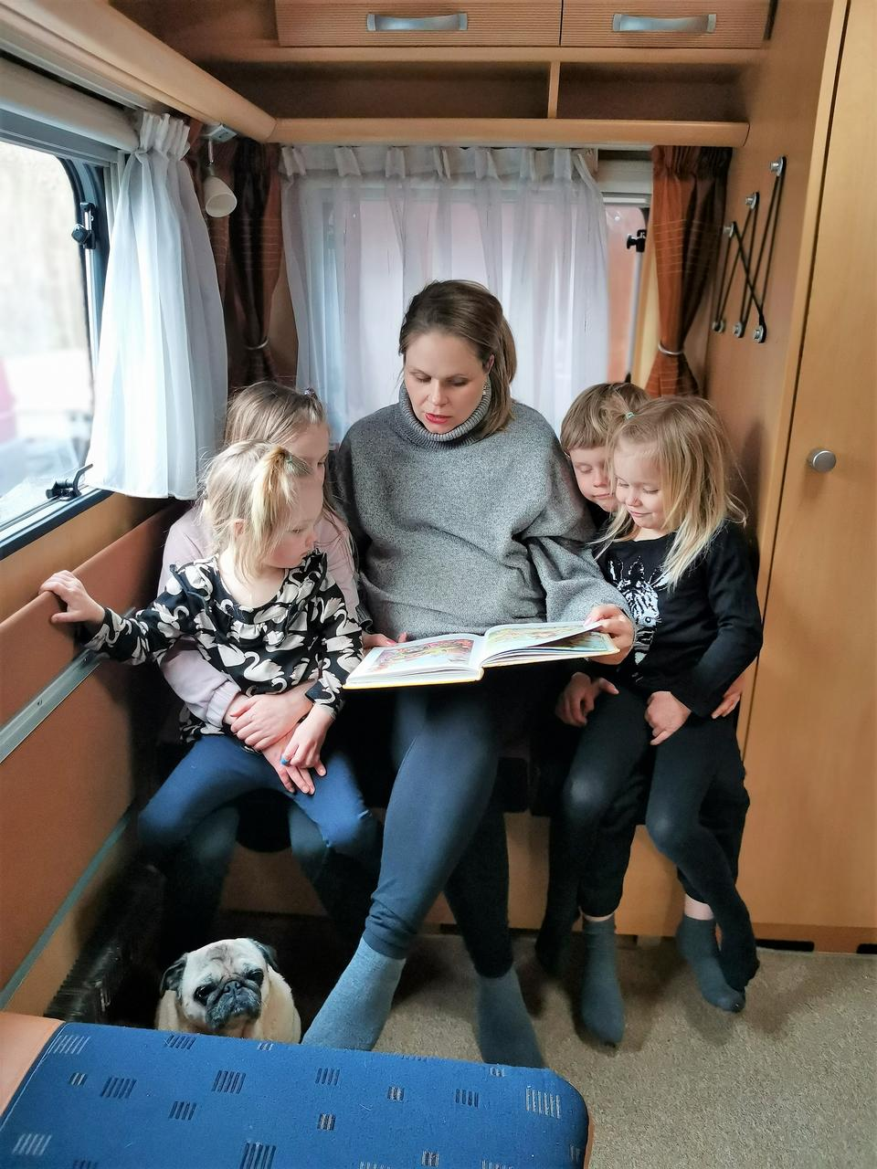 Eeva lukee kirjaa lapsille asuntovaunussa.