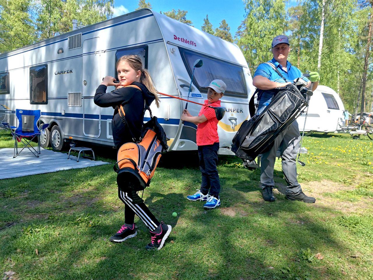 Golfin harjoittelua asuntovaunun edessä.