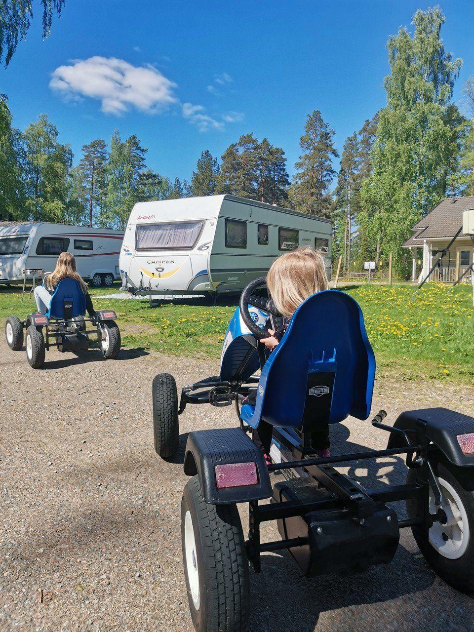 Lapset polkuautoilemassa leirintäalueella