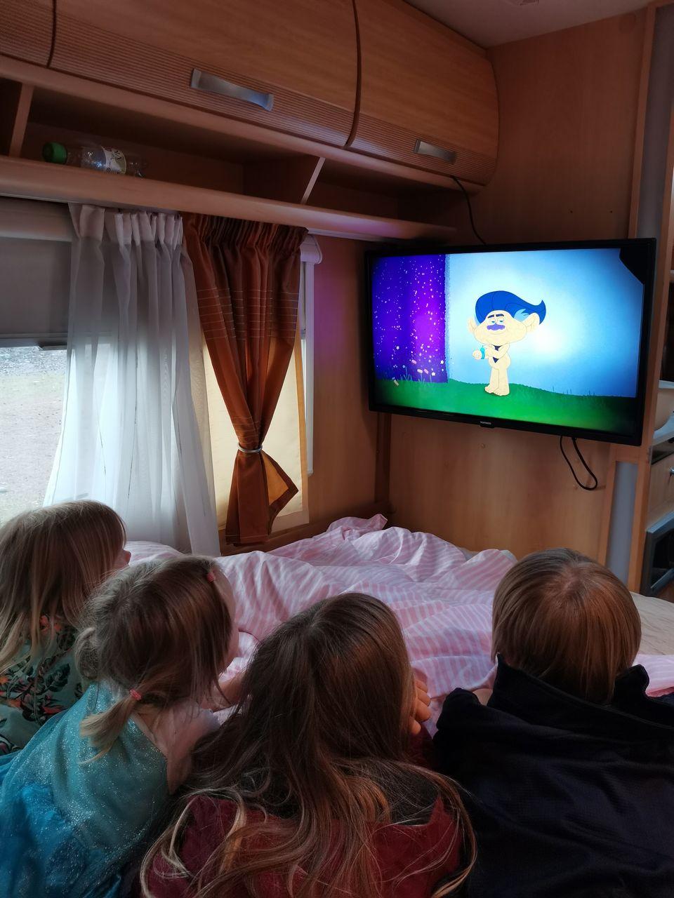 Lapset katselevat televisiota asuntovaunussa.