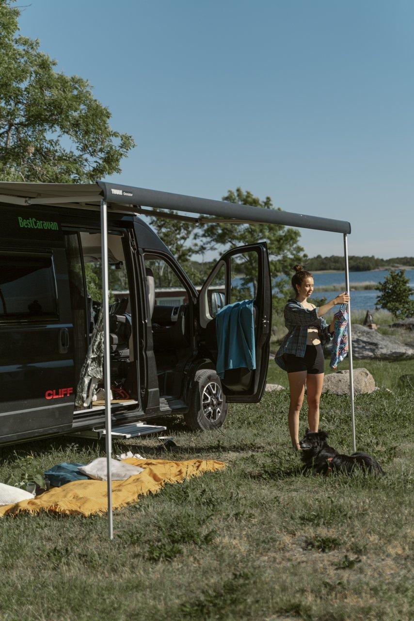 Matkailuauton markiisia ollaan pystyttämässä leiriytymistä varten