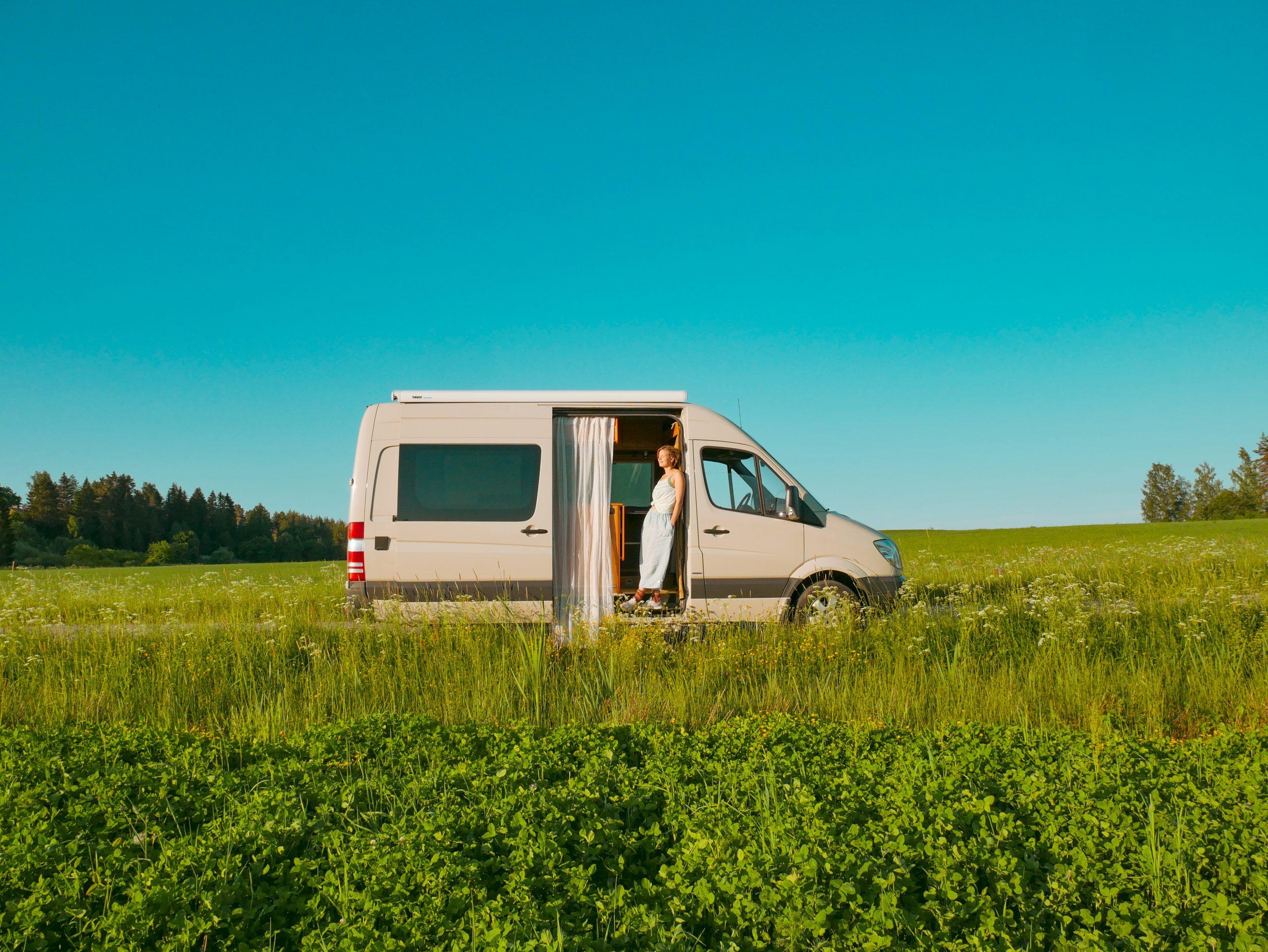 Käytettynä hankittu retkeilyauto ylpeän omistajansa kanssa niittymaisemissa.