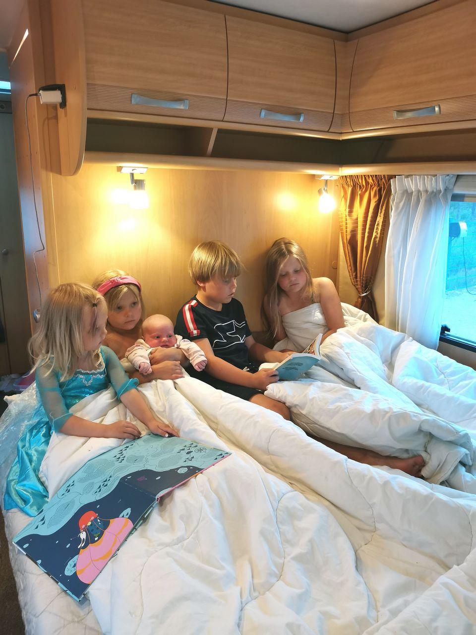Lapset asuntovaunun sängyssä lukemassa kirjaa.